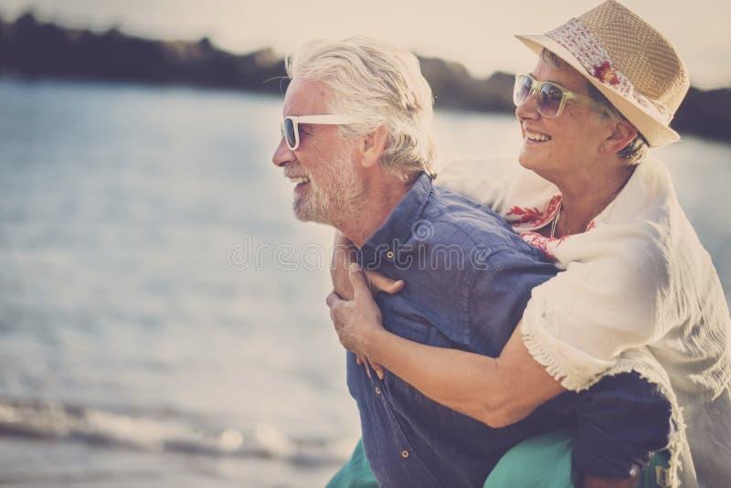 愉快的资深夫妇获得乐趣并且享受室外娱乐活动在海滩 人运载他的妇女回到享用 免版税图库摄影