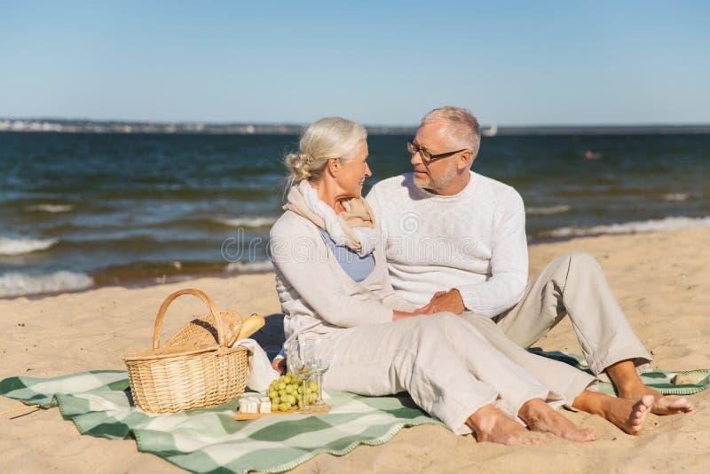 愉快的资深夫妇谈话在夏天海滩 免版税库存图片
