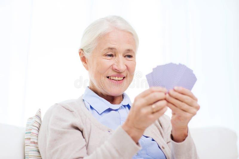 愉快的资深女子纸牌在家 免版税图库摄影