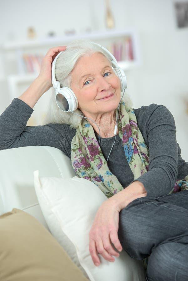 愉快的资深妇女佩带的耳机 免版税库存图片