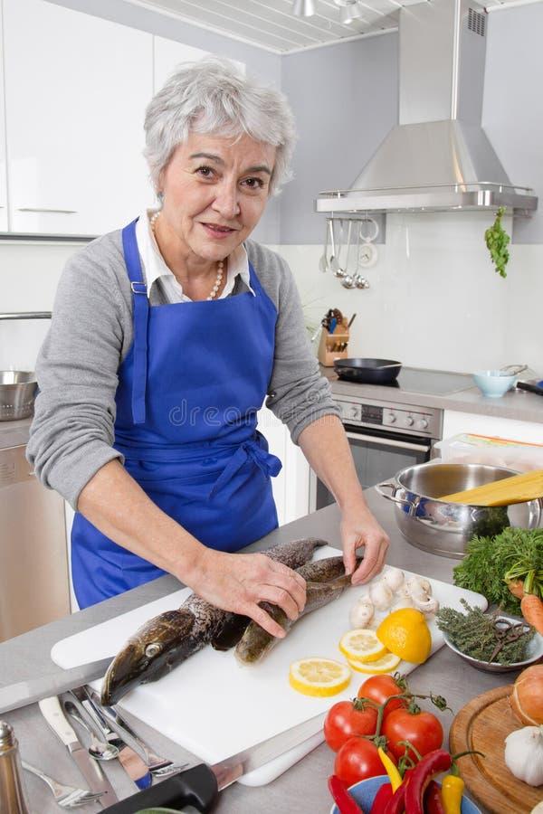 愉快的资深妇女在准备鲜鱼的厨房里 库存照片