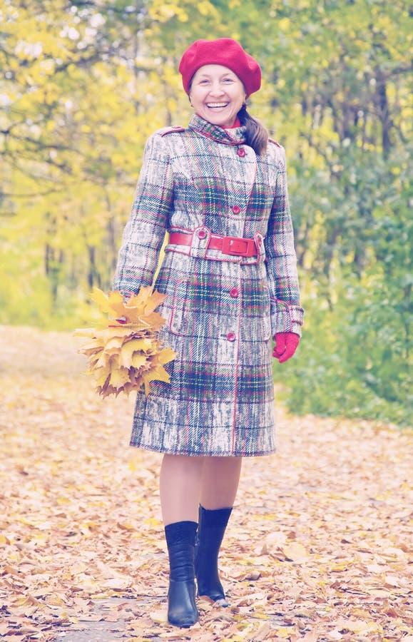 愉快的资深妇女在秋天 库存照片