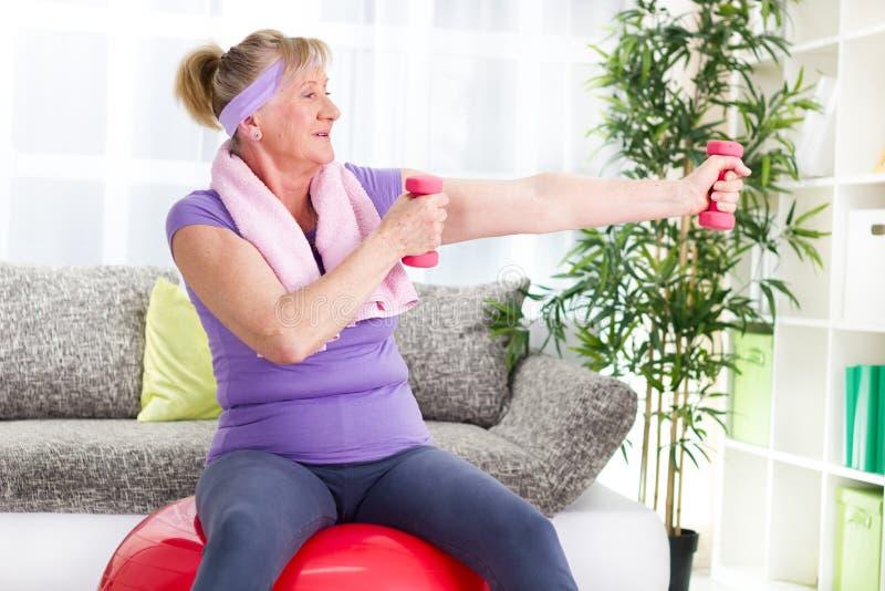 愉快的资深妇女坐健身房球和锻炼 免版税图库摄影