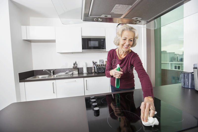 愉快的资深妇女清洁厨台 免版税库存照片