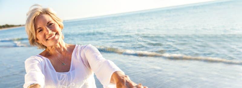 愉快的资深妇女跳舞热带海滩全景 库存图片