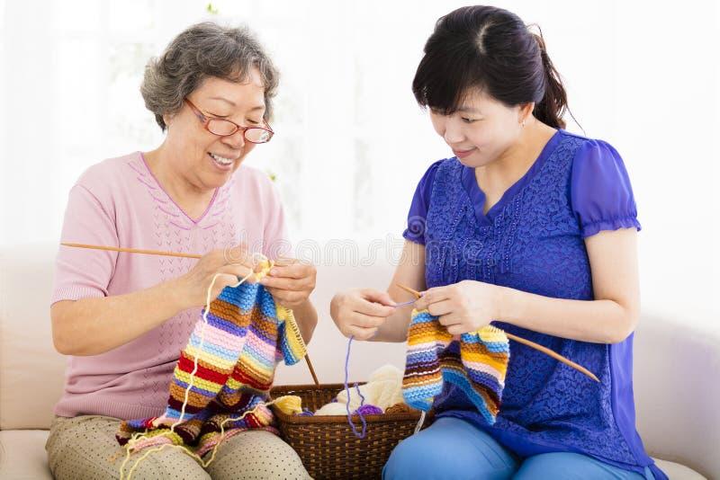 愉快的资深学会编织的母亲和女儿 免版税库存照片