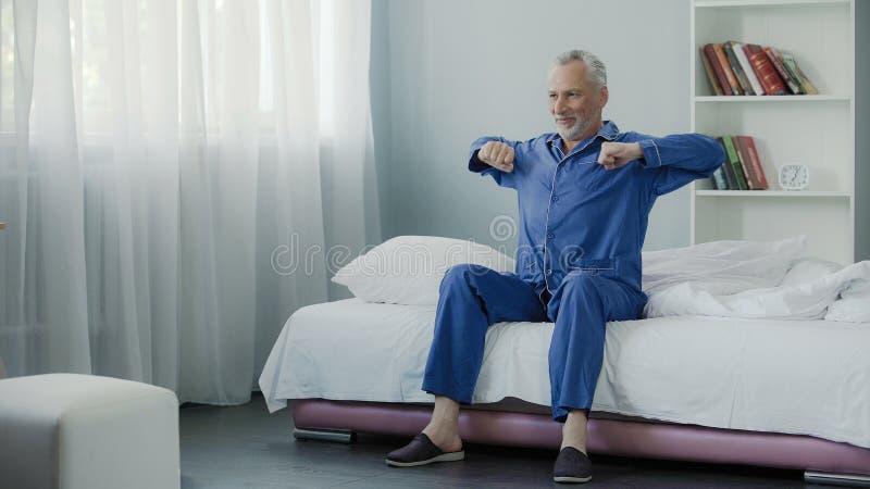 愉快的资深男性在他的床上的做早晨体操,好心情,乐观 免版税库存照片