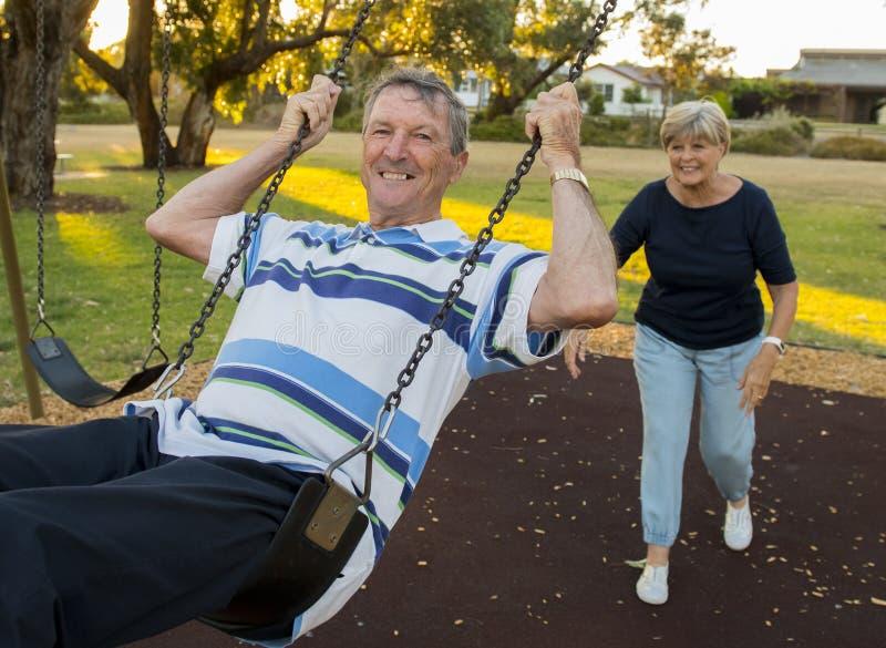 愉快的资深美国夫妇大约享用在摇摆的70岁停放与推挤丈夫的妻子一起微笑和获得乐趣 免版税库存照片