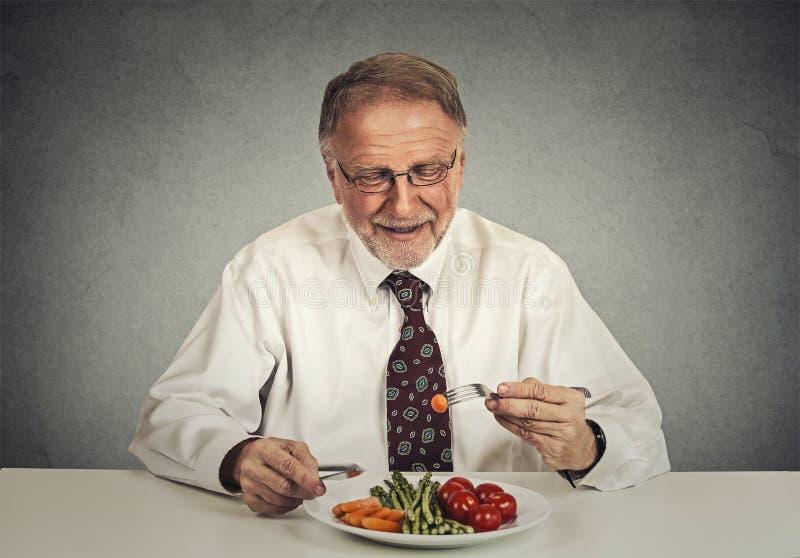 愉快的资深食人的新鲜蔬菜沙拉 库存图片