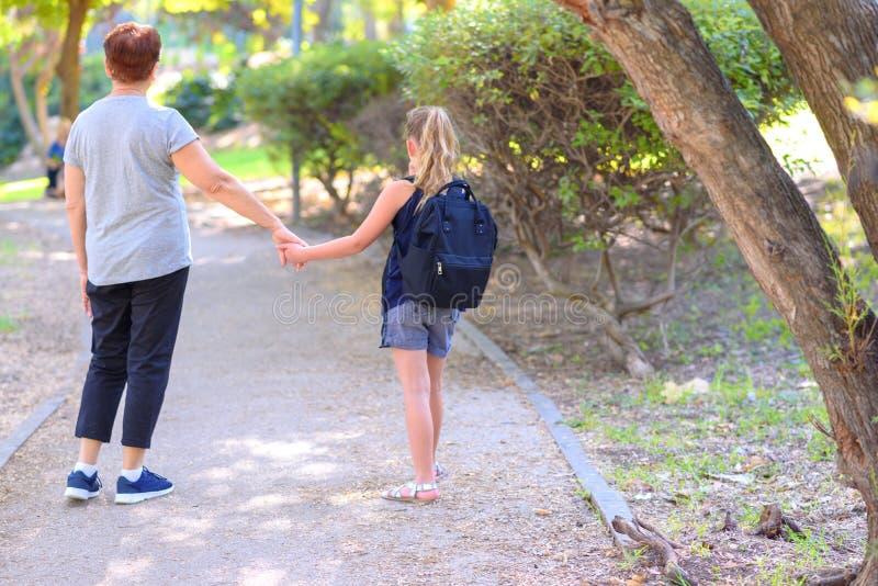 愉快的走到在街道上的学校的祖母和孙女在秋天公园 免版税库存照片