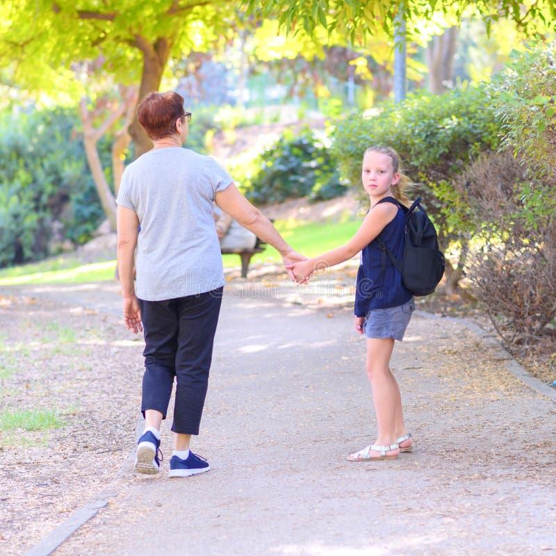 愉快的走到在街道上的学校的祖母和孙女在秋天公园 库存照片