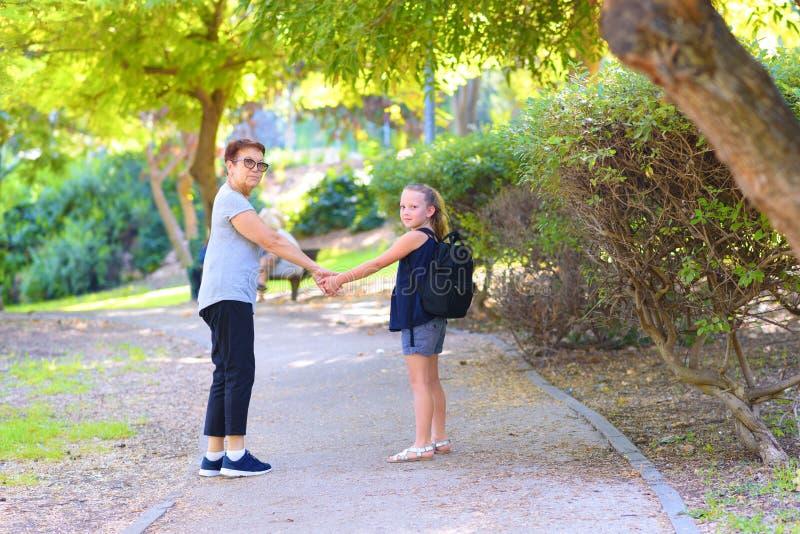 愉快的走到在街道上的学校的祖母和孙女在秋天公园 免版税库存图片