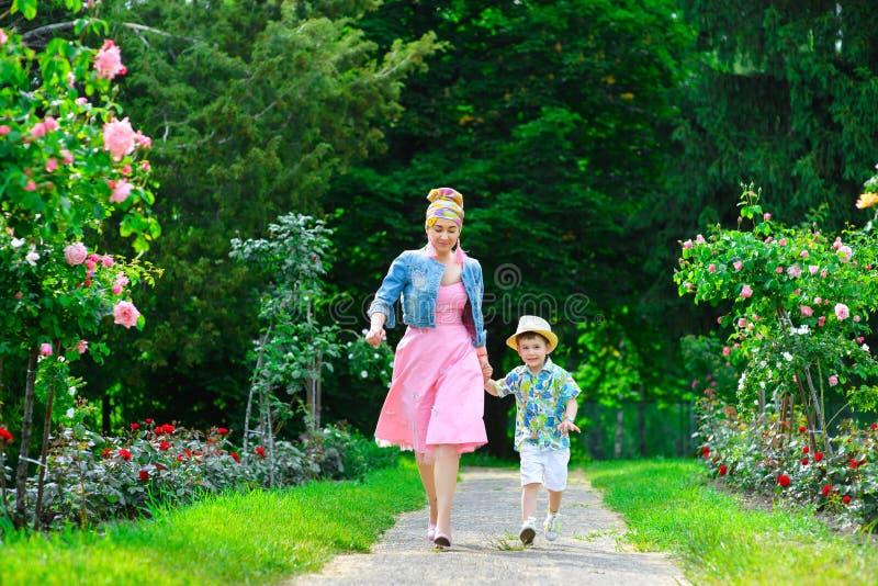 愉快的走在夏天的母亲和儿子停放与 免版税库存照片