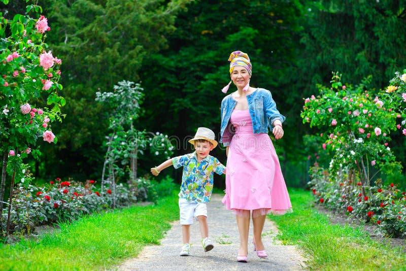 愉快的走在夏天的母亲和儿子停放与 图库摄影