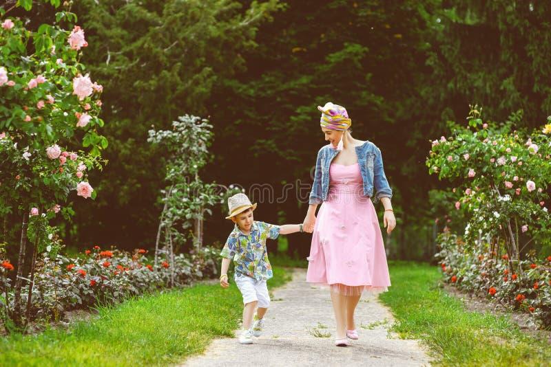 愉快的走在夏天的母亲和儿子停放与 免版税库存图片