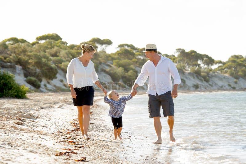 年轻愉快的走在家庭度假概念的海滩的母亲和父亲 库存图片