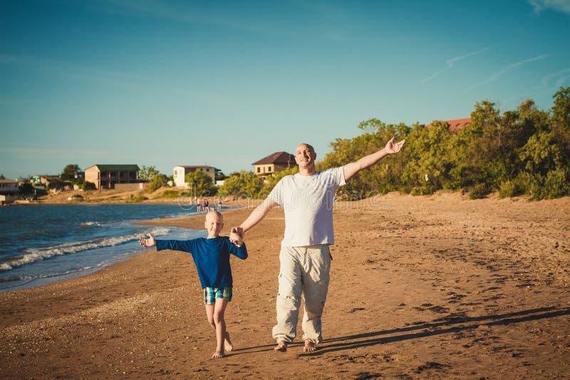 愉快的走在海滩的父亲和儿子 免版税库存图片