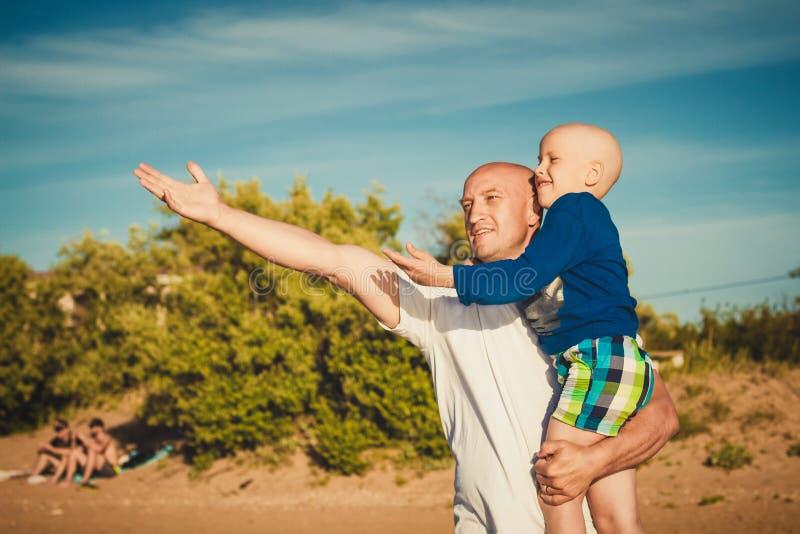 愉快的走在海滩的父亲和儿子 免版税图库摄影