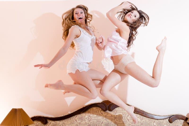 愉快的跃迁:2名美丽的滑稽的女朋友性感的妇女有乐趣跳跃的或飞行的惊奇高在他们的在床上的睡衣 免版税库存图片