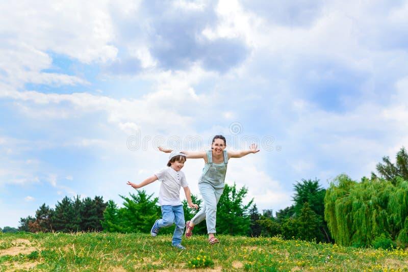 愉快的跑在草微笑的母亲和儿子 免版税库存图片