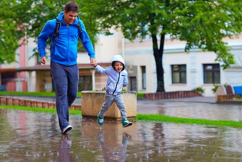 愉快的跑在雨下的父亲和儿子 库存图片