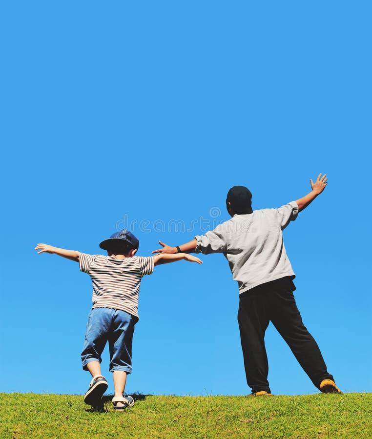 愉快的跑小山的父亲和儿子 免版税库存图片