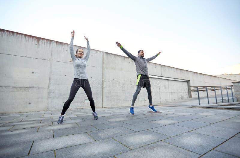 愉快的跳跃男人和的妇女户外 免版税库存图片