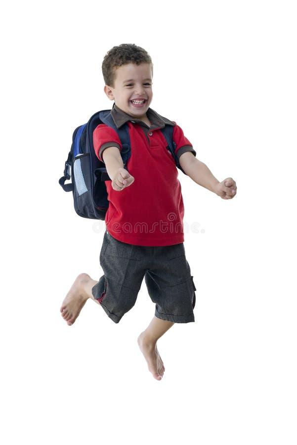 年轻愉快的跳跃的男小学生 库存照片