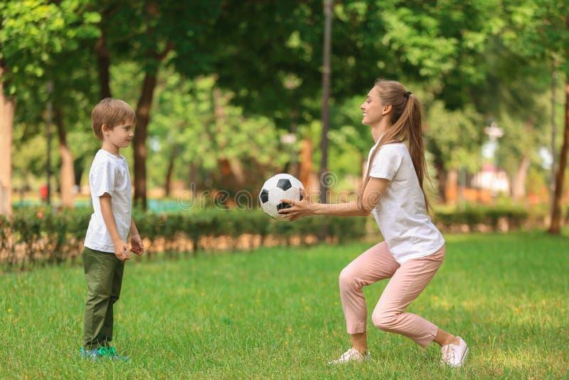 愉快的踢橄榄球的母亲和儿子在公园在夏日 图库摄影