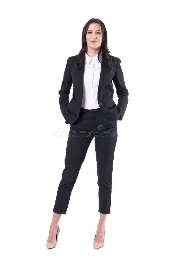 愉快的轻松的确信的成功的女商人用在看照相机的口袋的手 免版税库存照片