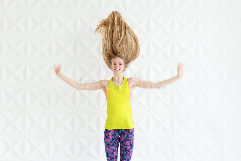 愉快的运动的适合妇女画象有白肤金发的长的头发的 免版税库存照片