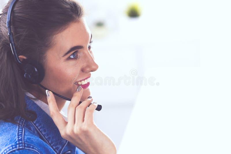 愉快的迷人的年轻女人坐和与膝上型计算机一起使用使用耳机在办公室 库存照片