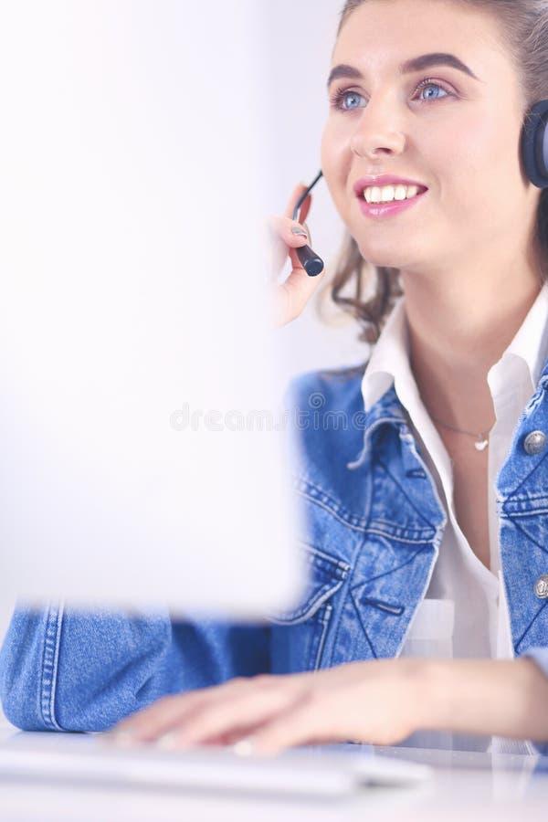 愉快的迷人的年轻女人坐和与膝上型计算机一起使用使用耳机在办公室 库存图片