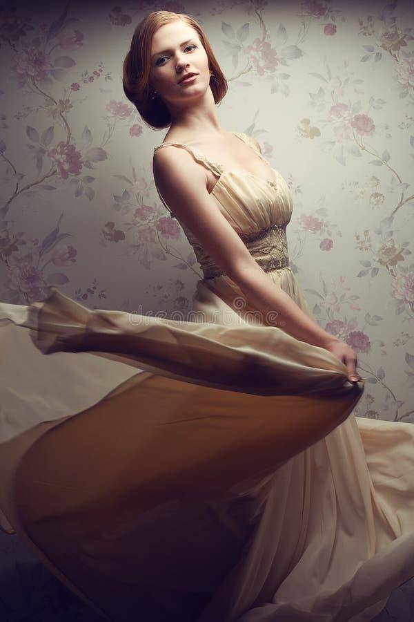 愉快的迷人的红发女孩葡萄酒画象凉快的礼服的 图库摄影
