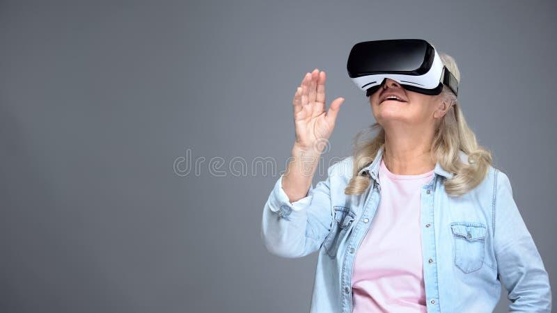 愉快的退休人员女性佩带的VR耳机,现代技术,创新 免版税库存图片