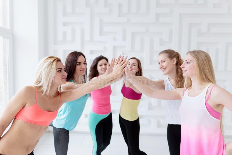 愉快的适合的妇女穿运动服庆祝成功的小组 库存图片