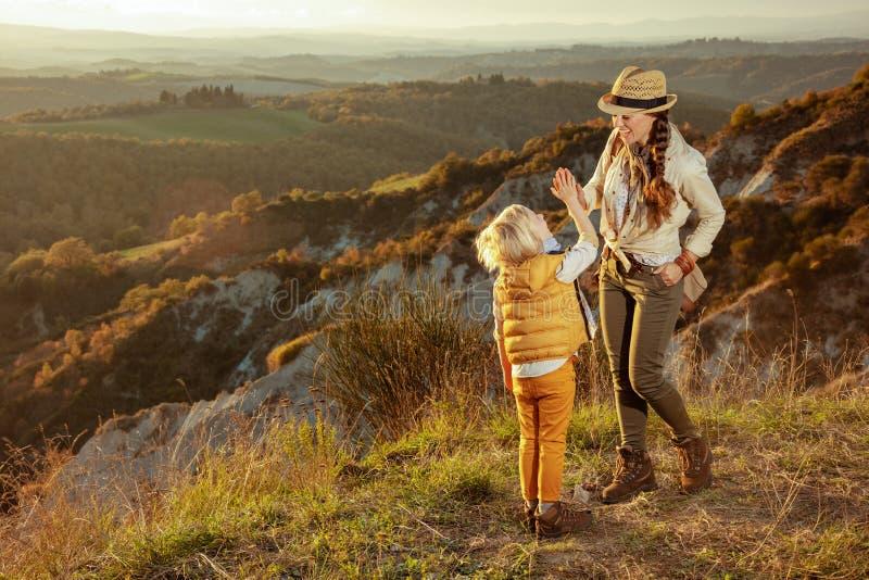 愉快的适合的母亲和孩子在夏天迁徙高五的托斯卡纳 免版税库存图片