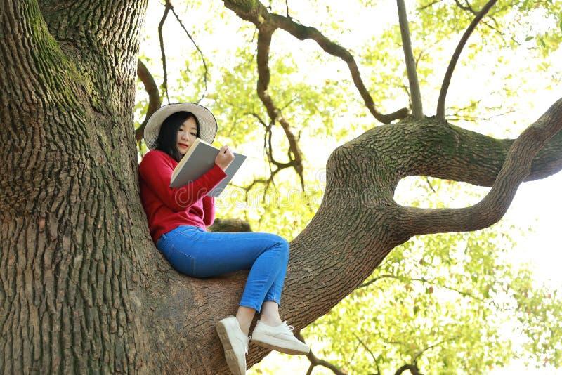 愉快的逗人喜爱的亚洲中国自然美丽的妇女女孩在春天公园享用业余时间读的书 免版税库存图片