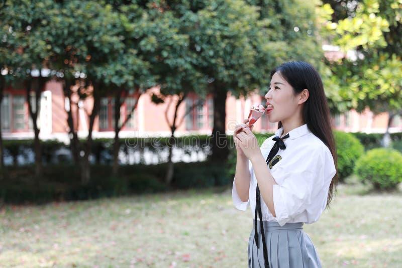 愉快的逗人喜爱的可爱的美丽的女孩高中大学生享受业余时间吃冰淇凌 免版税库存照片