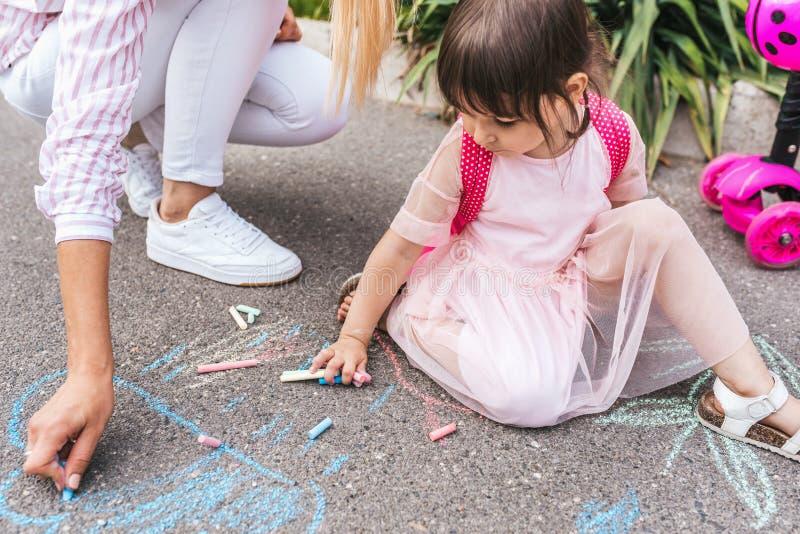 愉快的逗人喜爱的女孩和母亲图画的播种的水平的图象与白垩的在边路 一起白种人女性戏剧 免版税库存照片