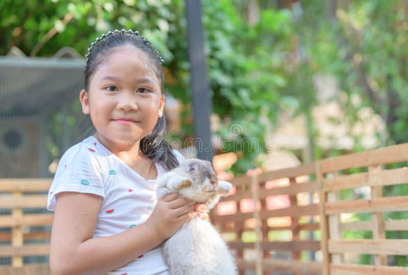 愉快的逗人喜爱的女孩拥抱兔子在农场 库存图片