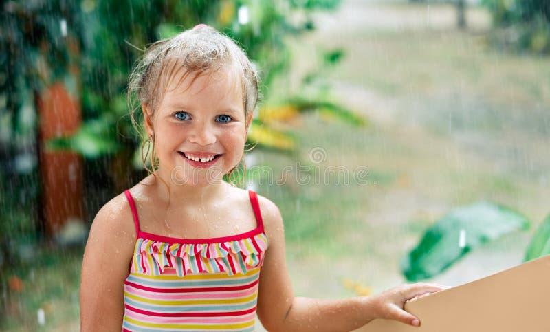 愉快的逗人喜爱的女孩接近的画象享用夏天雨 免版税库存照片