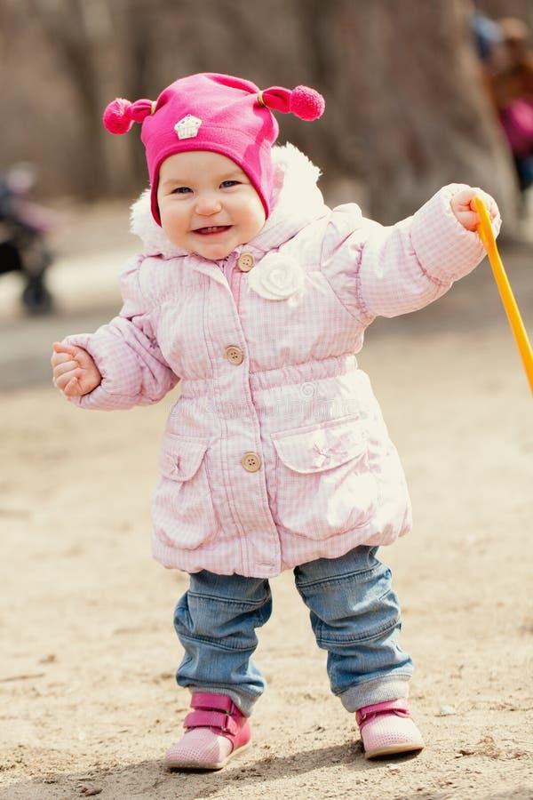 愉快的逗人喜爱的女婴在春天公园走 图库摄影