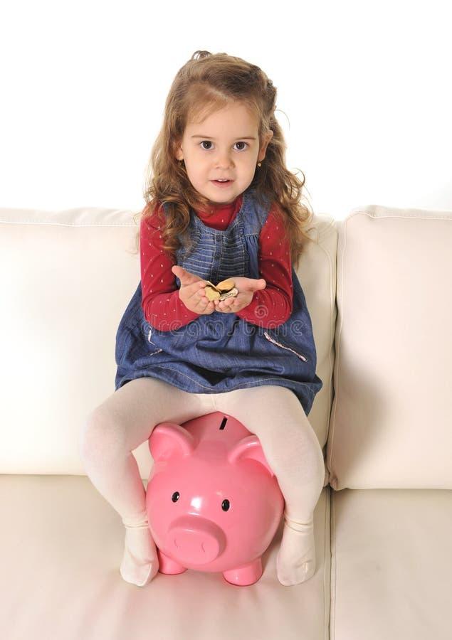 愉快的逗人喜爱的小女孩坐拿着硬币的巨大的存钱罐 库存照片