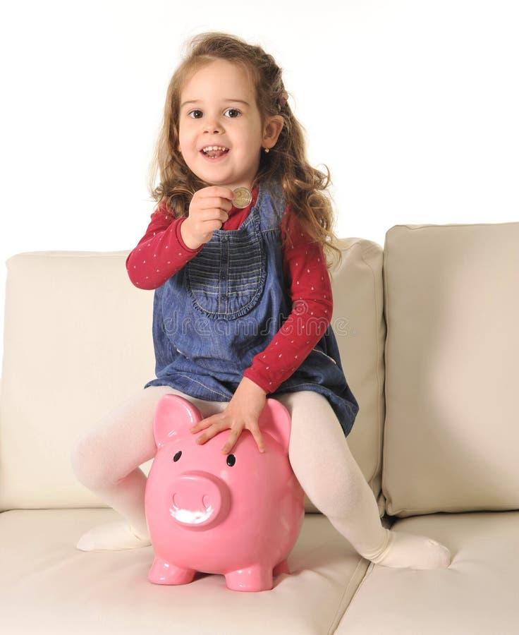 愉快的逗人喜爱的小女孩坐插入硬币的巨大的存钱罐 库存图片