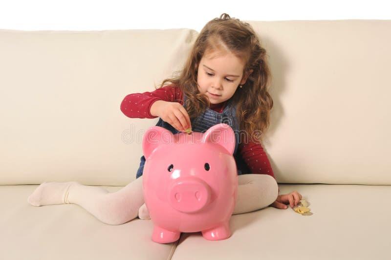 愉快的逗人喜爱的小女孩坐插入硬币的巨大的存钱罐 免版税图库摄影