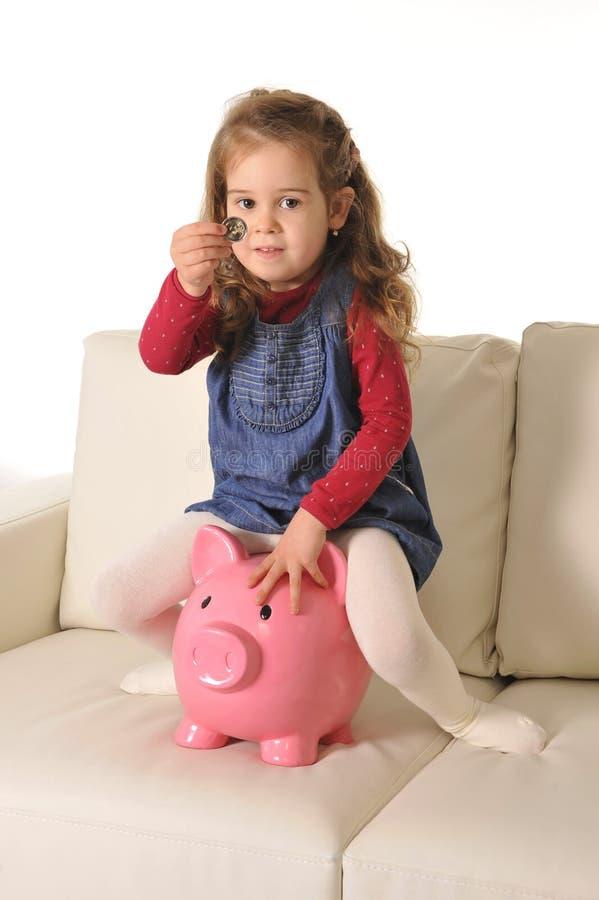 愉快的逗人喜爱的小女孩坐插入硬币的巨大的存钱罐 免版税库存照片