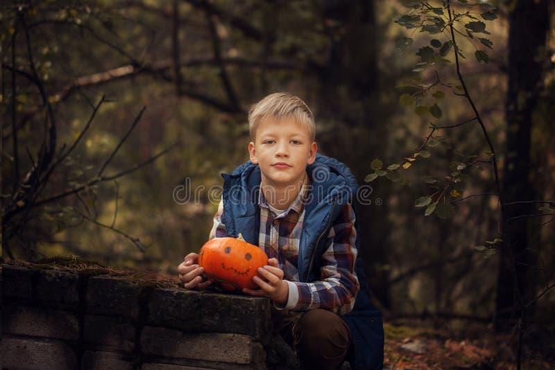 愉快的逗人喜爱的小孩男孩用万圣夜南瓜在秋天黑暗森林里 免版税库存图片