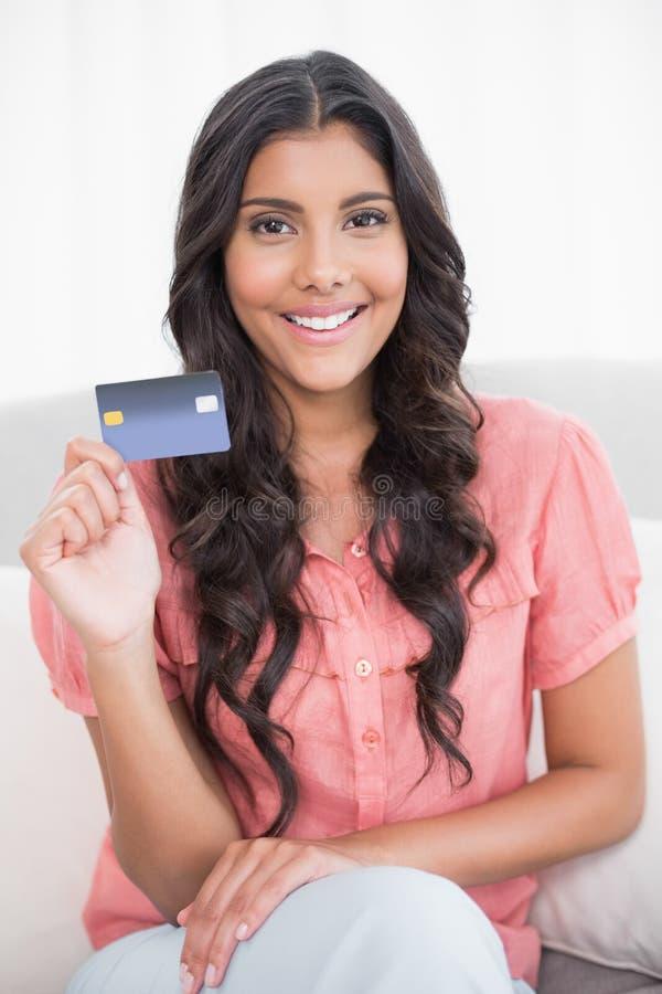 愉快的逗人喜爱的浅黑肤色的男人坐显示信用卡的长沙发 库存图片