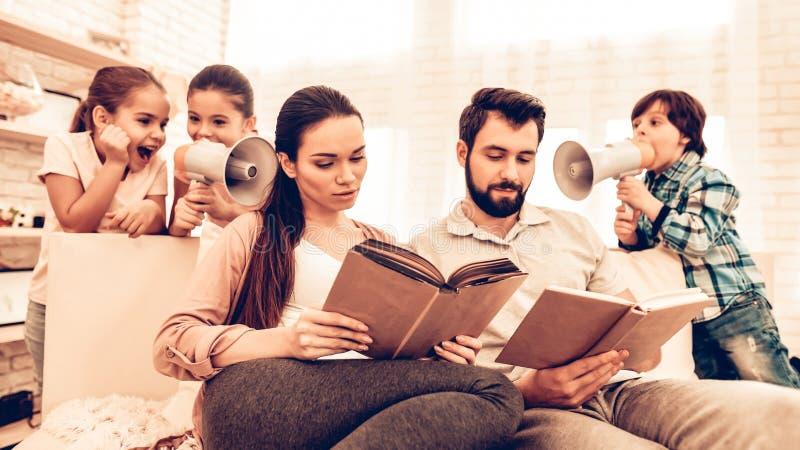 愉快的逗人喜爱的父母看书,当孩子使用时 免版税库存照片